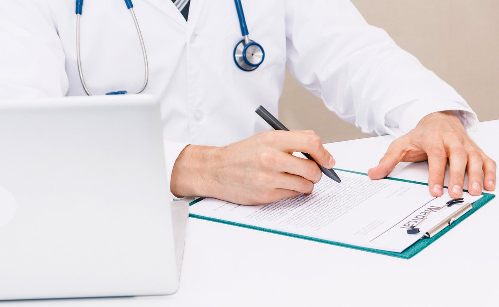 Doctor with stethoscope working and writing on paperwork in hospital.healthcare and medicine